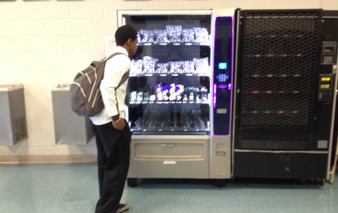 A student buys gear from the Chantilly spirit vending machine located in the gym lobby.