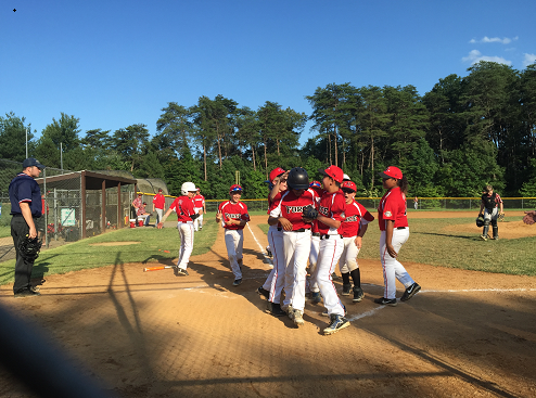 A Travel Baseball Team celebrates after a home run.