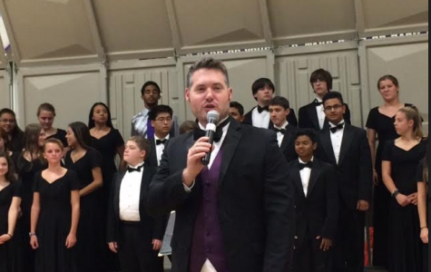 Choral director Evan Ayers leads in the performance.