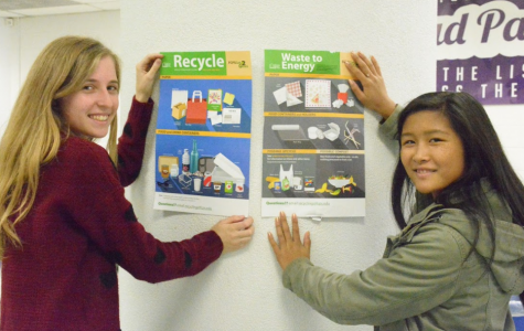 Seniors Ellen Wray (left) and Kailey Cheng (right) hang up posters to encourage recycling.