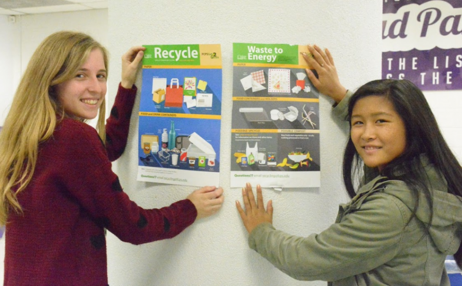 Seniors+Ellen+Wray+%28left%29+and+Kailey+Cheng+%28right%29+hang+up+posters+to+encourage+recycling.