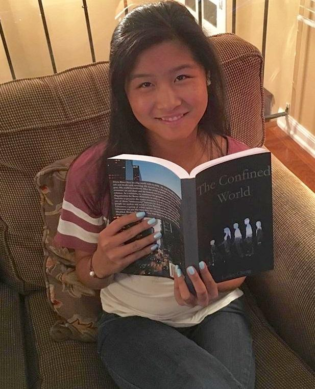 Senior+Kailey+Cheng+poses+with+her+newly+published+book%2C+%22The+Confined+World.%22