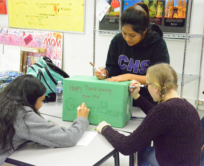 Sophomores Natasha Smith and Tracey Valdez and senior Iva Shuping work together to create a community service box. This box will be filled with Thanksgiving food and given to a family in need.