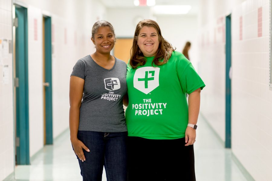 English teacher Danielle Hicks and School-Based Technology Specialist Margaret Sisler pose for a picture in their coordinating Positivity Project shirts. The Positivity Project has replaced the Character Education program.