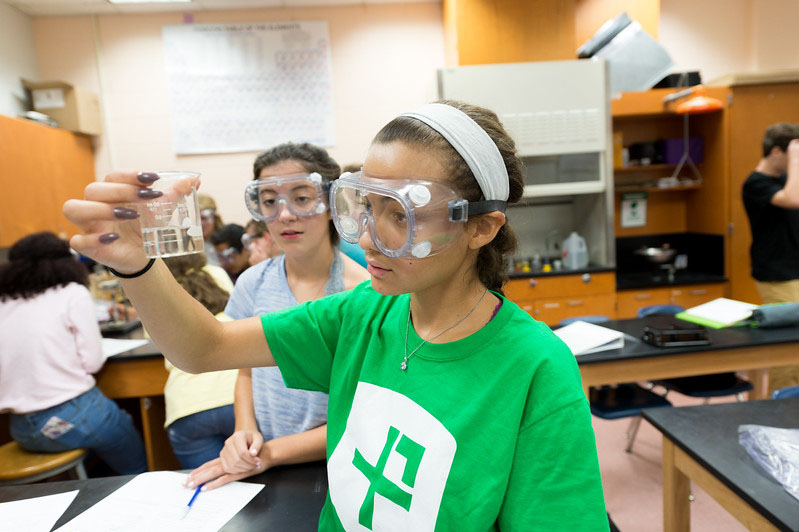 Sophomore+and+P2+team+member+Noemi+Pimentel+performs+a+chemical+experiment+while+spreading+positivity+through+her+shirt.