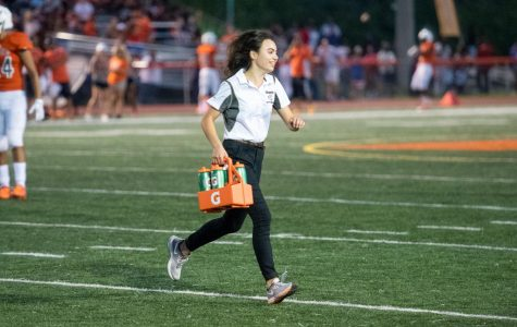 Senior Camille Ohanian, an assistant athletic trainer, helps with managerial duties of the sports managers, handing out water and helping out the team.