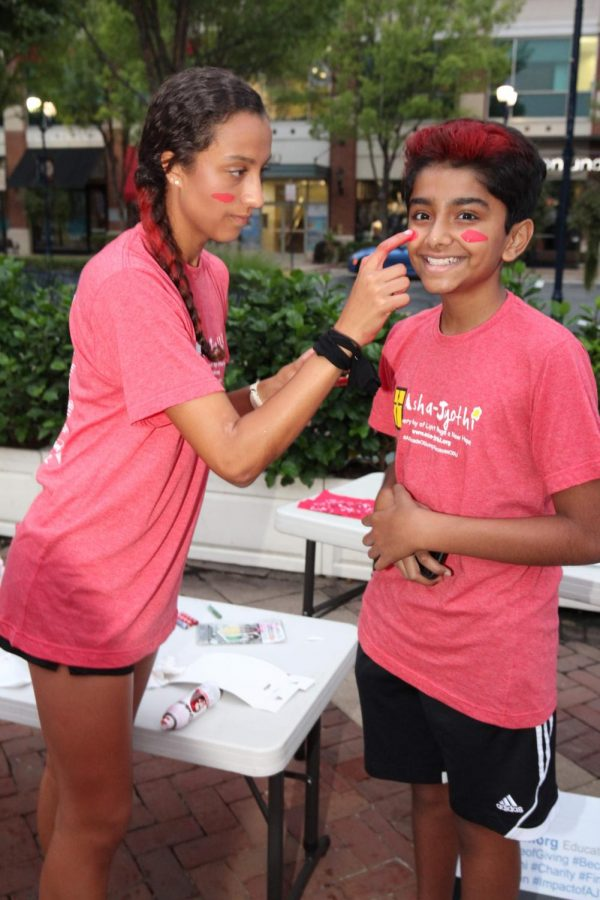 Senior Beka Luebbe and freshman Arjun Rajan prepare for the race by using red face paint and hair spray.