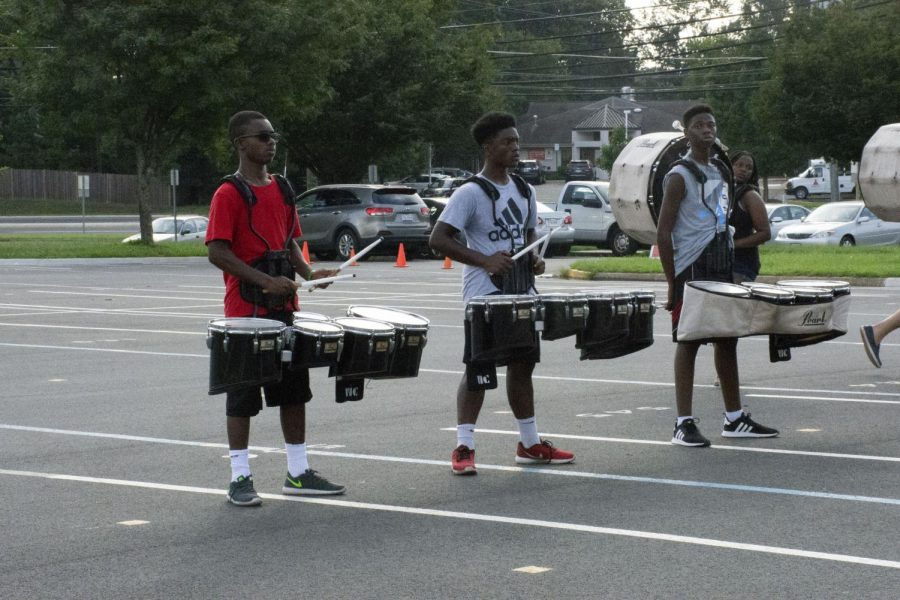 Tenor drum players and juniors Jonah Northern and Ricky McGlothin and sophomore Lans Fofana play in sync during practice.