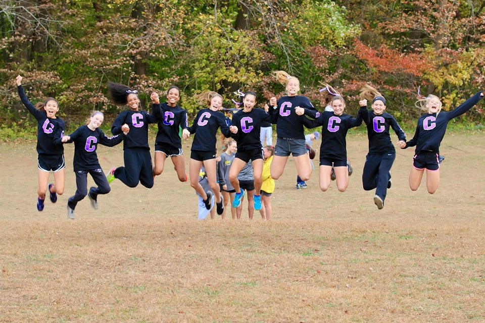 Varsity cross country girls jump for joy following their advancement to state championships after placing third in the region.