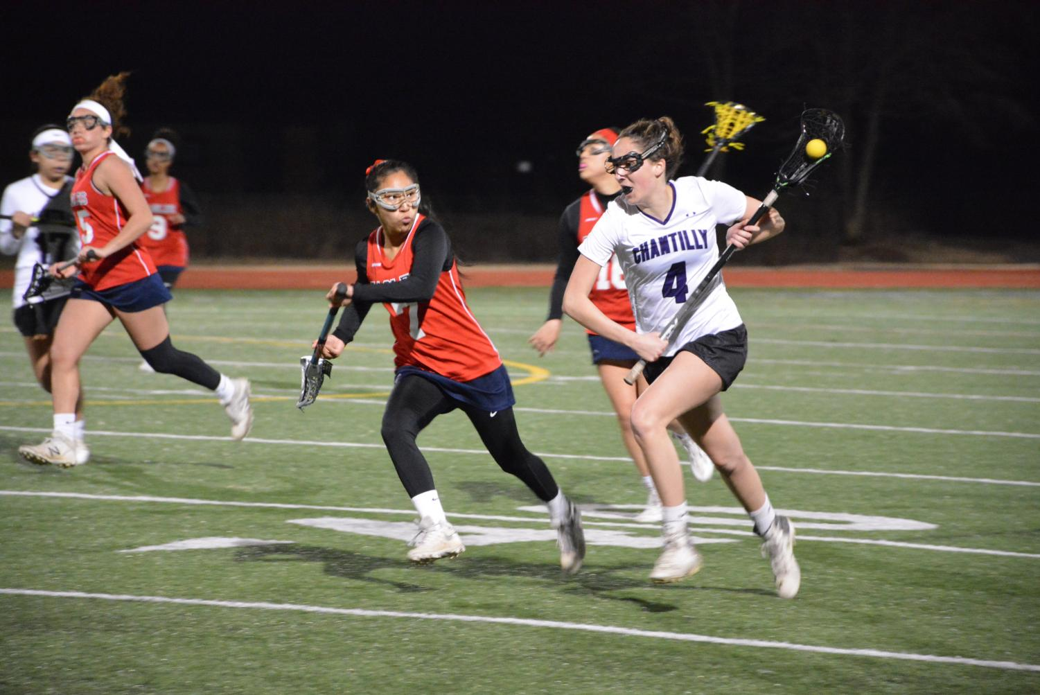 Senior and captain Katie Carita advances the ball down the field during the March 12 home game against Thomas Edison. The team managed its first win of the season, ending the game with a score of 11-2.