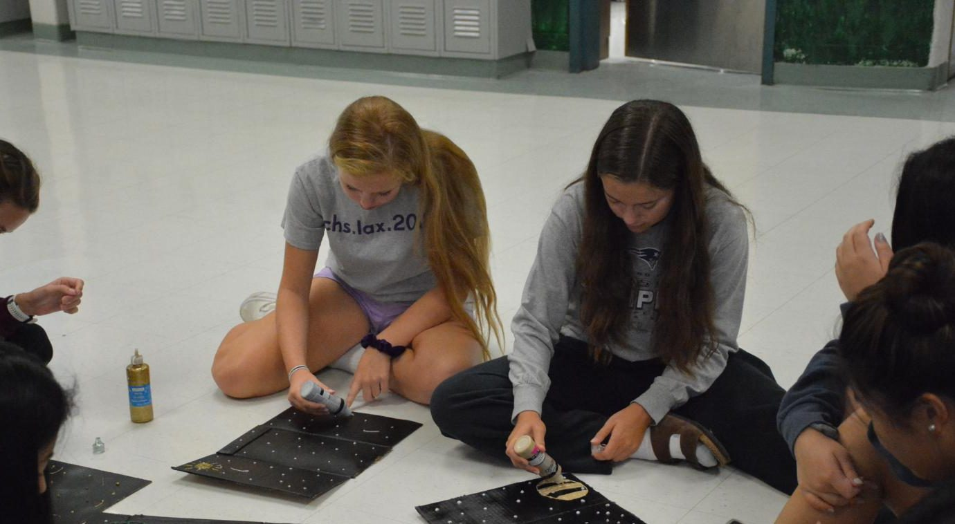 Sophomores Natalie Hogan and Caelin Rowell work on posters for powder puff, a game which takes place during homecoming week. Traditionally, females play football while males cheerlead, but this year the activities are coed.