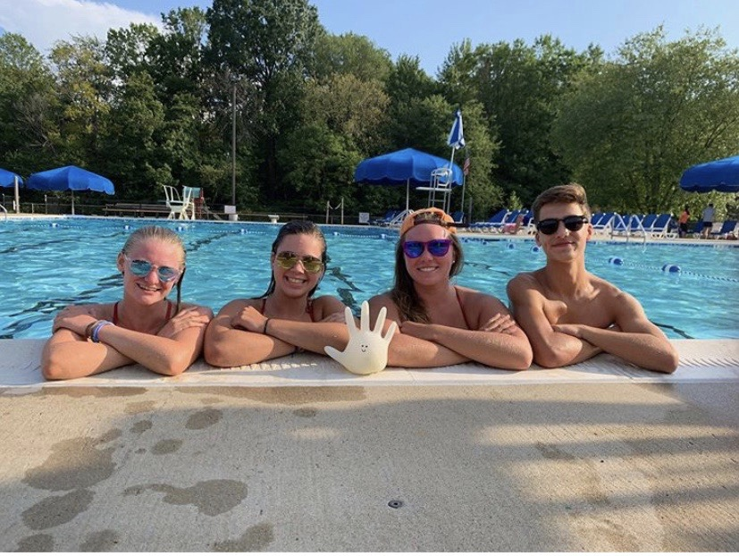 Junior Olivia Grindal, sophomore Alexis Fitzgerald, alumni Jacquee Clabeaux, and sophomore Ryan Brown pose with Boo the glove near the pool. The lovable mascot has been part of several Greenbriar pool trips and adventures throughout the summer.
