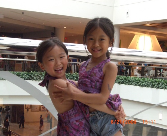 Senior and fraternal twins Annie and Yannie Wu embrace in a hug as they spend the day together at Tysons Corner. When they were younger, they often wore matching clothes and engaged in the same activities.