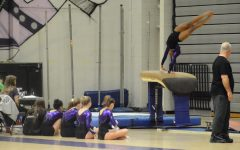 Junior Alex Reaves performs a flip on vault while her teammates watch from the side. The support she gets from her teammates cheering her on is vital for the success of her performance.