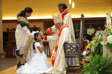This photo depicts Nayana Celine Xavier getting confirmed on her First Holy Communion and Confirmation day. Communion and Confirmation mark an individual