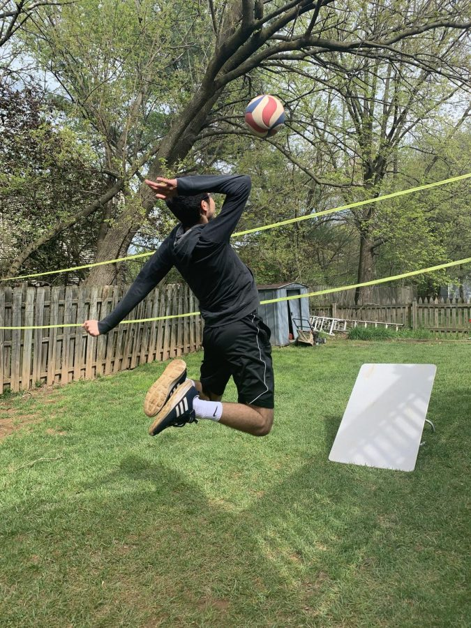 Sophomore Ayham Elayan jumps to spike the ball over the net he's set up in his backyard. Even though volleyball practices may be cancelled like other sports, Elayan continues to maintain his skills by practicing on his own.