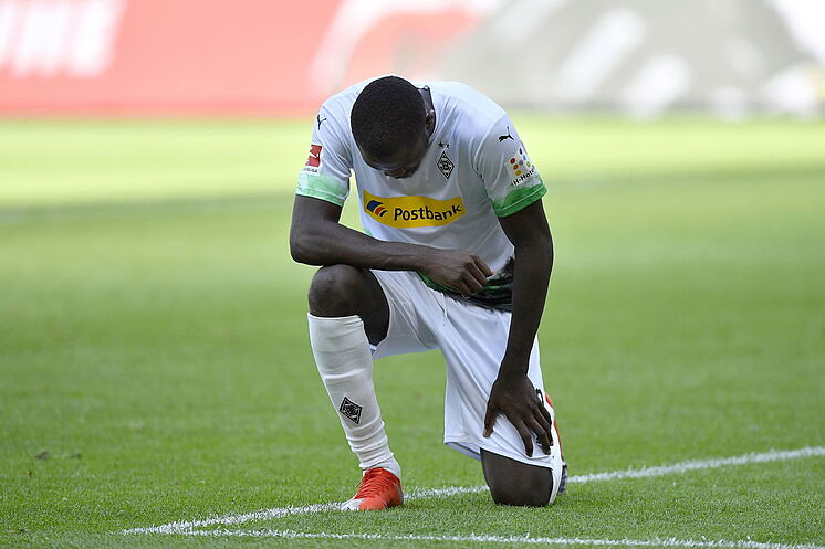 Borussia Monchengladbach player Marcus Thuram takes a knee after scoring a goal in solidarity with the Black Lives Matter movement.