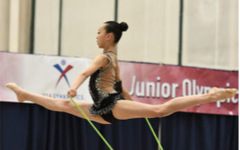 Rhythmic gymnast Kaylee Baek is performing her rope routine in the National Junior Olympics competition.