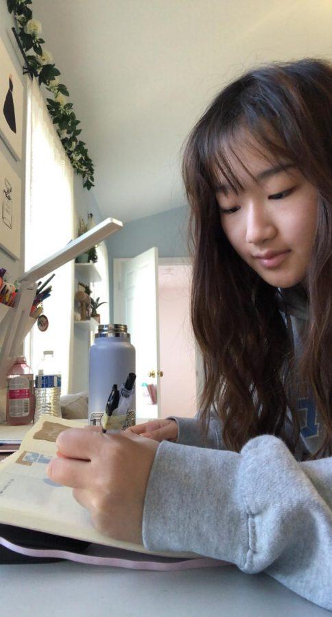 Sophomore Bonny Koo writes down notes as she learns virtually.