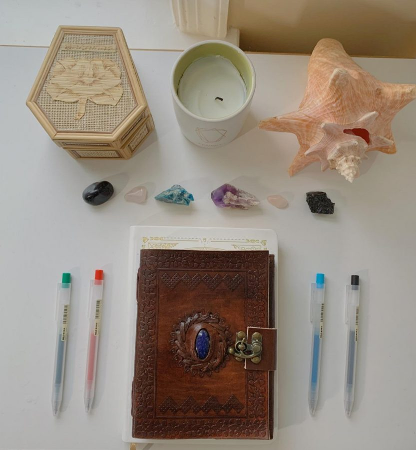 Junior Taylor Ko manifests with a set up that includes her manifestation diary, crystals and candle.