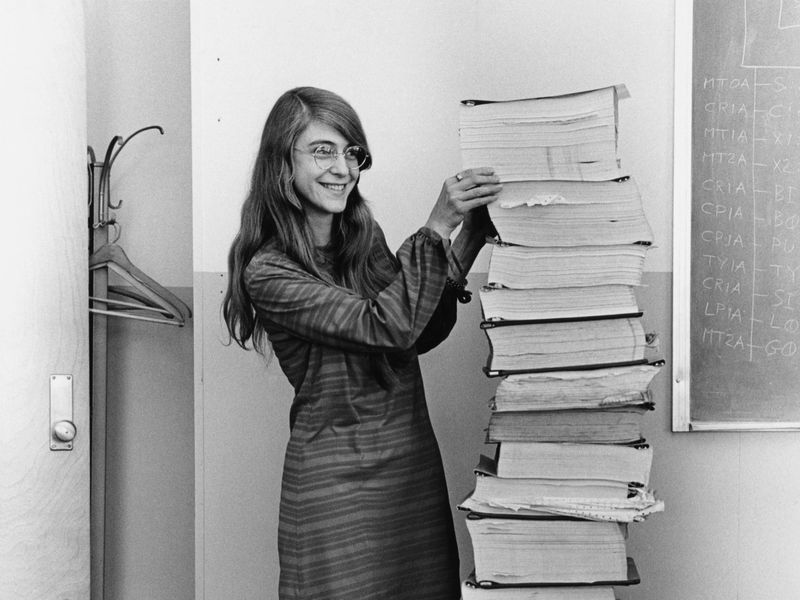 Margaret Hamilton stands next to the program listings she and her teammates developed in addition to flight software for the Apollo 8 project.