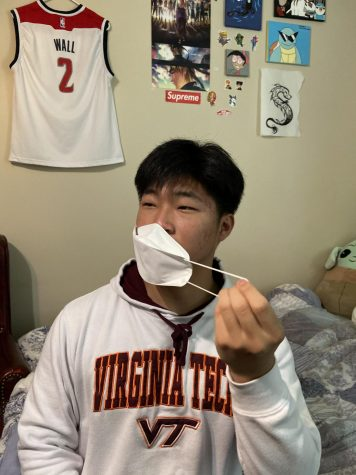 Freshman Eric Kim takes off his mask on May 18 to embrace the new CDC regulations.