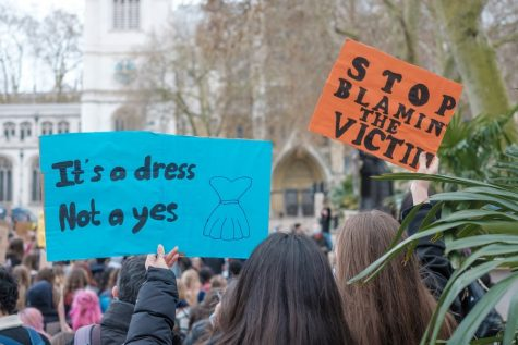 In the aftermath of British marketing executive Sarah Everard's murder, protesters hold up signs decrying the violence inflicted upon women.