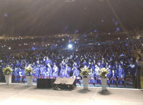 Students throw their caps into the air to celebrate graduation at Jiffy Lube Live on June 2.