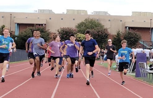 Sophomore Alex Morris, senior Orion Hairston, sophomore Rudra Dave, junior Raymond Creeks, sophomore Sebastian Nowicki, junior Brian Creeks and sophomore Colt Craddock warm up for their practice by doing strides on the track on Monday, Sep. 20.