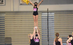 On Sept. 16, junior Amber Villanueva practices her routine with her stunt group of freshman Brianna Wade, junior Lauran Carr and junior Sammie Senio during cheer practice.