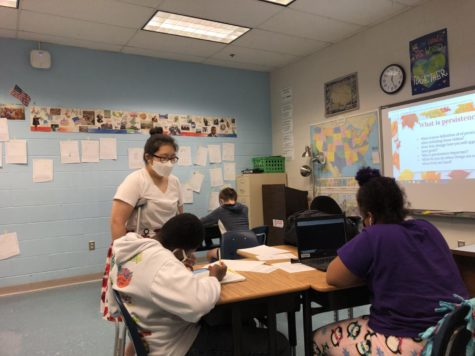 Special education social studies teacher Angela Moon helps sophomore Jaylen Cumberbatch and freshman Lily Myers with classwork during her sixth period class on Sept. 23.