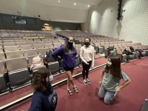 Senior Edie Obenberger, junior Lucy Sherrier, senior Kaela Francisco and junior Anna Dimauta discuss meeting Kacey Caliba while the rest of the ensemble prepares the stage for rehearsal on Sept. 21, in the auditorium.
