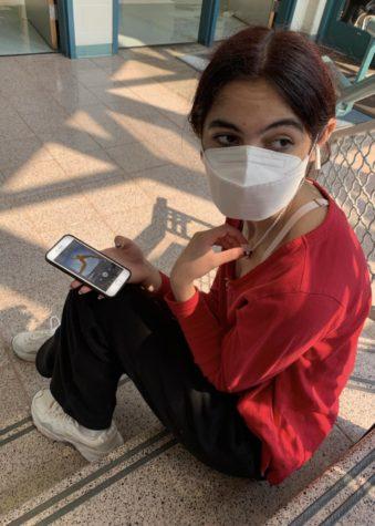 """Junior Hannah Moghaddar listens to """"Solar Power"""" on her phone."""