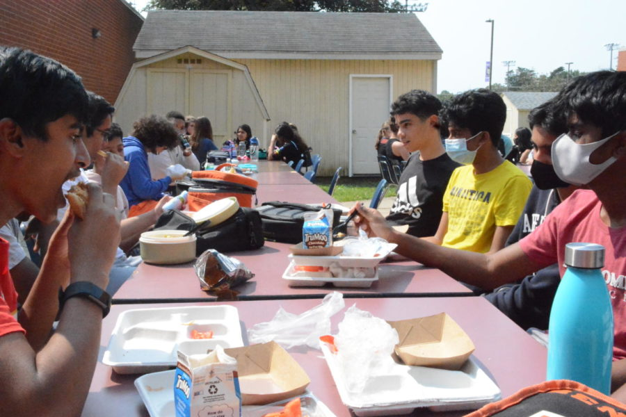 Outside door 11, several students eat lunch close together in groups on Sept. 14.
