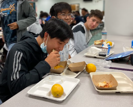 Freshmen Jason Li, Peter Tran and Jayden Cavero enjoy a no-cost lunch, which includes milk, fruit, carbohydrates and meat, in the cafeteria.